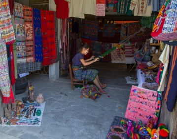 A young lady weaving the famous brightly-colored cloths of Guatemala